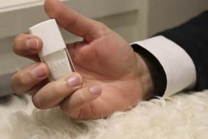 imagen de una mano sujetando un frasco de esmalte