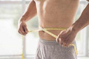 Hombre con cinta métrica para prevenir estrías en los hombres