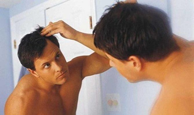 hombre mirando su cabello al espejo